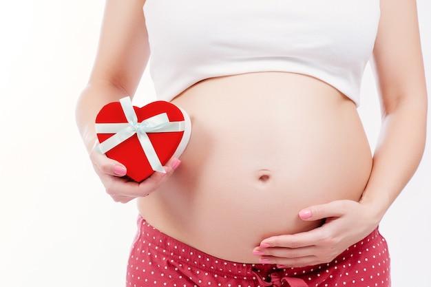 Schwangere mutter, die ihren bauch zeigt und ein geschenk anhält