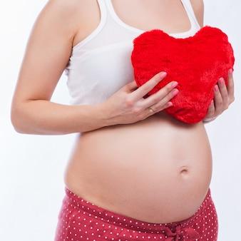 Schwangere mutter, die ihren bauch zeigt und ein spielzeug hält