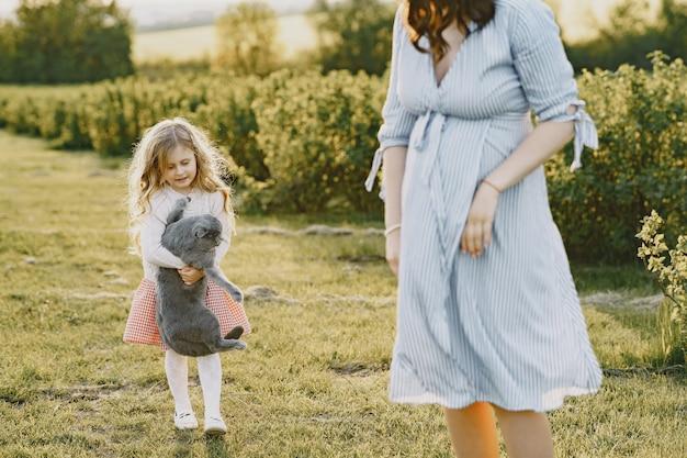 Schwangere mutter mit ihrer tochter auf einem feld