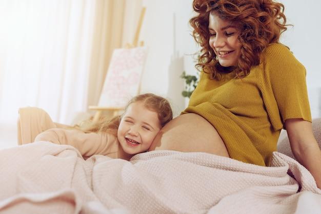 Schwangere mutter spielt mit ihrer tochter. konzept von familie, freude und schwangerschaft