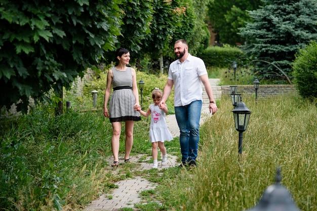 Schwangere mutter, tochter und vater gehen in den park.