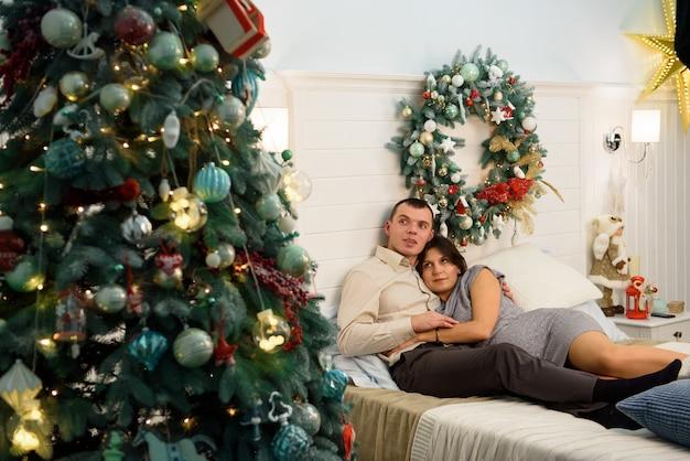 Schwangere mutter und ihr ehemann zu hause mit weihnachtsdekorationen