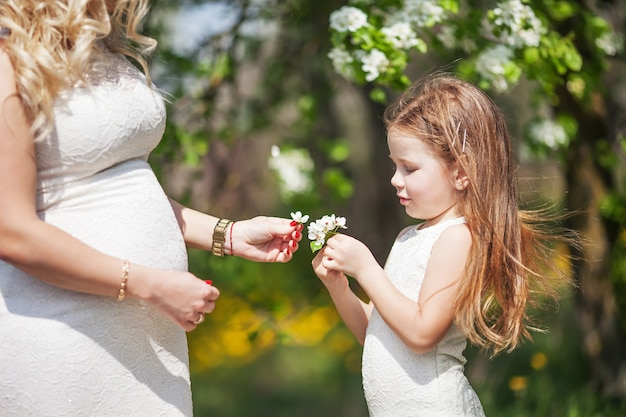 Schwangere mutter und ihre kleine tochter haben spaß im freien. familienblick porträt