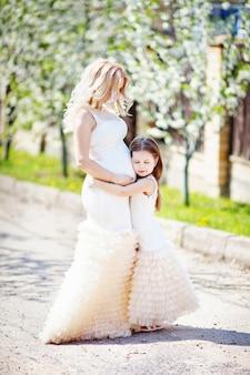 Schwangere mutter und ihre kleine tochter im sommergarten. familienblick porträt