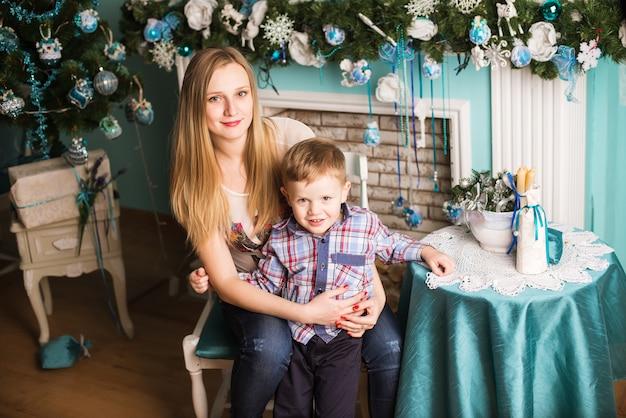 Schwangere mutter und kind der junge, die zu hause weihnachten feiert