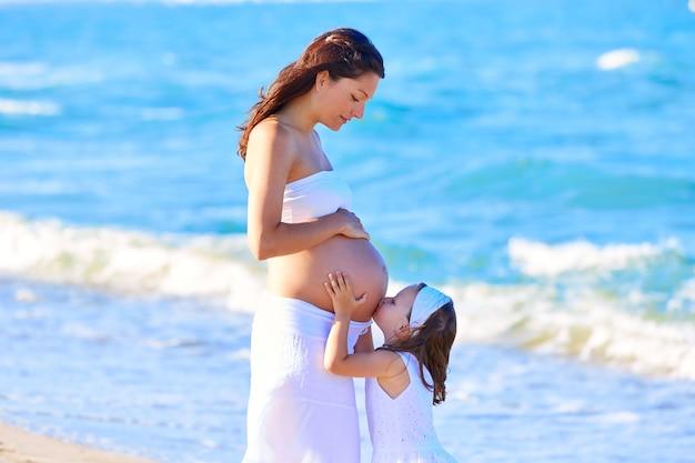 Schwangere mutter und tochter am strand