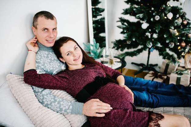 Schwangere paare, die auf bett nahe weihnachtsbaum liegen. frohes neues jahr und frohe weihnachten. weihnachten dekoriertes interieur. schwangerschaft, familienurlaub, menschen- und erwartungskonzept.