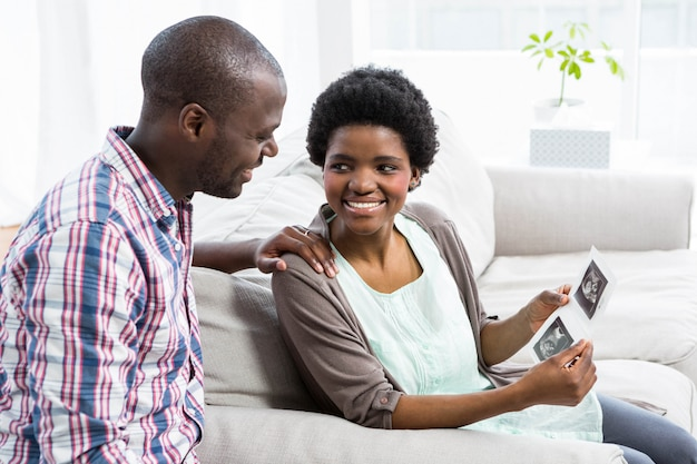 Schwangere paare, die auf sofa sitzen und zu hause ultraschallscan betrachten