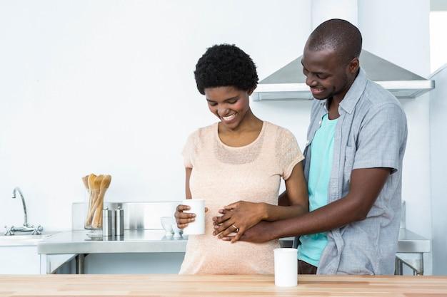 Schwangere paare, die beim trinken des tasse kaffees an der küche sich umfassen