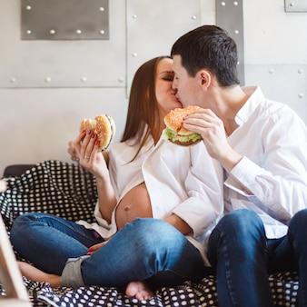 Schwangere paare, die fastfood essen