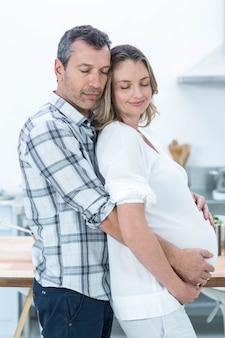 Schwangere paare, die kamera in der küche betrachten