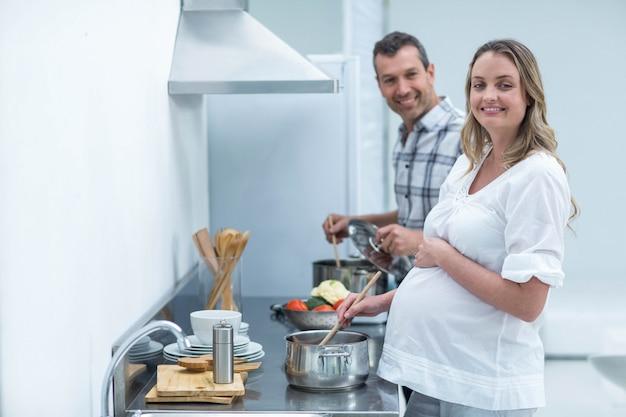 Schwangere paare, die lebensmittel in der küche zubereiten
