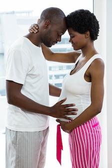 Schwangere paare, die sich zu hause streicheln