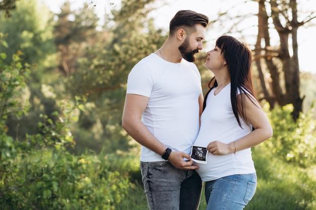 Schwangere paare, die ultraschallscan halten. konzept des schwangerschaftsgesundheitswesens.