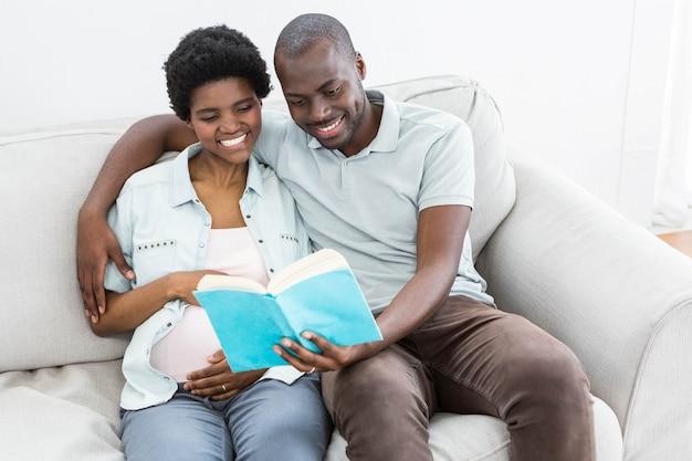 Schwangere paare, die zu hause ein buch lesen