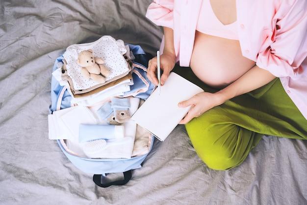 Schwangere packt krankenhaustasche mit checkliste with