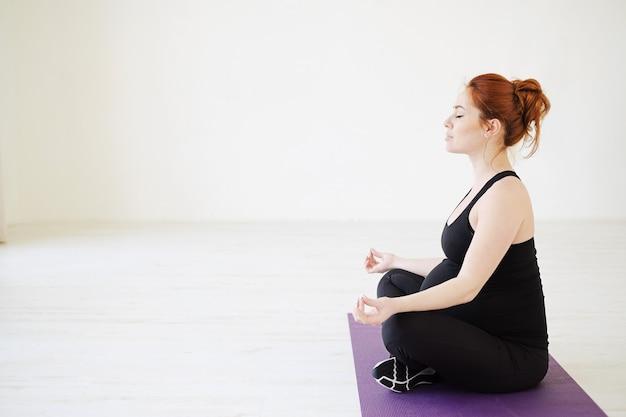 Schwangere sitzende frau im lotussitz meditieren