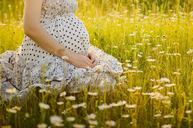 Schwangerer bauch in der natur. schwangeres mädchen im sonnenuntergang, schwangere frau, die sich draußen im park entspannt