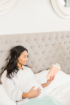 Schwangerer brunette, der ein buch auf dem bett liest