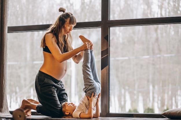 Schwangerer mopther, der yoga mit kleiner tochter tut