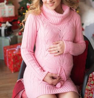 Schwangeres mädchen am heiligabend zu hause in der nähe des baumes des neuen jahres