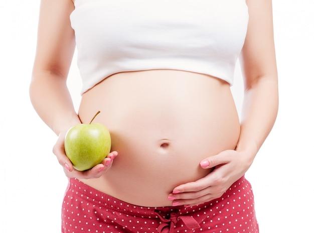 Schwangeres mädchen, das einen grünen apfel anhält