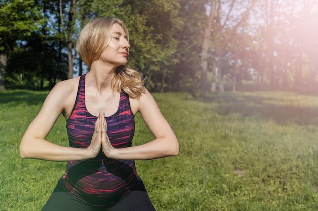 Schwangeres mädchen der junge, das yoga im sommerpark tut.