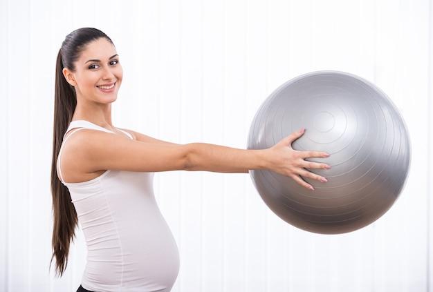 Schwangeres mädchen hält gymnastikball.
