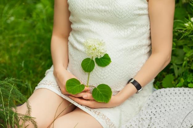 Schwangeres mädchen im kleid, das im garten sitzt
