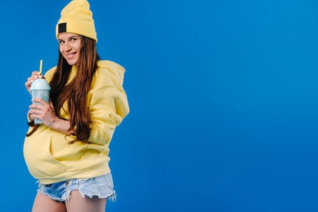 Schwangeres mädchen in gelber kleidung mit einem glas saft auf blauem hintergrund