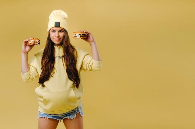 Schwangeres mädchen in gelber kleidung mit hamburgern in den händen auf gelbem hintergrund
