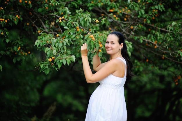 Schwangeres mädchen in weiße sommerkleid auf dem hintergrund von aprikosenbäumen. schwangere frau lächelnd