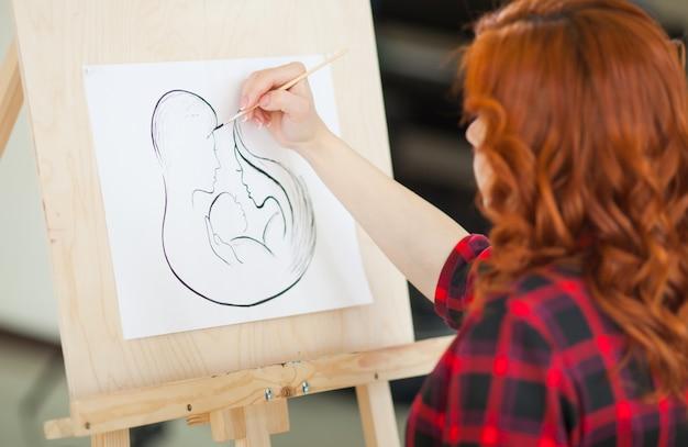 Schwangeres mädchen malt ein bild ihrer zukünftigen familie.