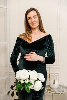 Schwangeres mädchen mit blumen und in einem samtkleid