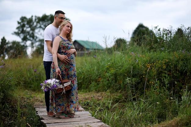 Schwangeres mädchen mit dickem bauch und jungem mann im park