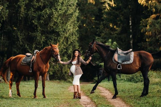 Schwangeres mädchen mit einem dicken bauch in einem hut neben pferden im wald in der natur. stilvolles mädchen in weißer kleidung und einer braunen jacke.