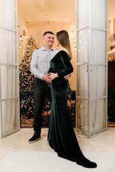 Schwangeres mädchen mit einem schönen abendkleid umarmt ihren mann
