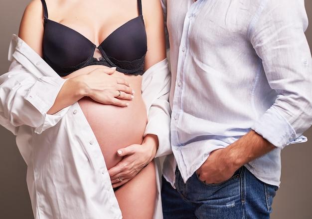 Schwangeres paar in einem rahmen ohne gesicht