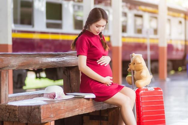 Schwangeres rotes kleid der frau, das auf einer bank am tragen des roten gepäcks am bahnhof sitzt