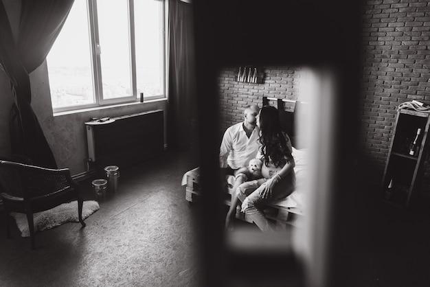 Schwangerschaft und leutekonzept - glücklicher mann, der seine schwangere frau zu hause steht am fenster umarmt