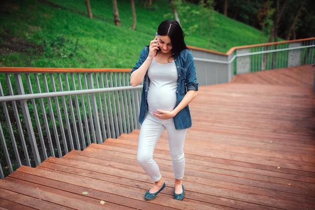 Schwangerschafts-, mutterschafts-, leute- und erwartungskonzept - nah oben von der schwangeren frau mit einkaufstaschen am park