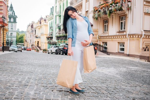 Schwangerschafts-, mutterschafts-, leute- und erwartungskonzept - nah oben von der schwangeren frau mit einkaufstaschen an der stadtstraße.