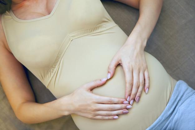 Schwangerschaftsbauch. frauenhände in herzform. schwangere frau, die herzförmige hände auf ihrem bauch hält. mutterschaft braune farben