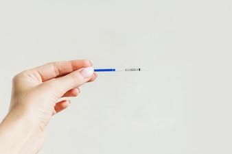 Schwangerschaftstest in der weiblichen Hand auf grauem Hintergrund. Kein Ergebnis. Leeres Modell.