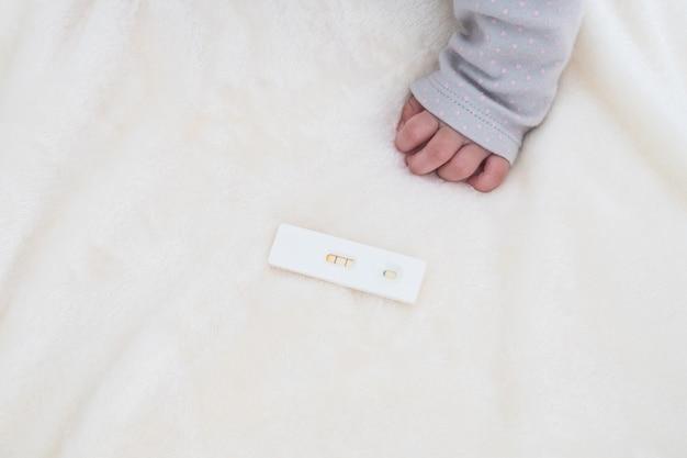 Schwangerschaftstest mit positivem schwangerem und babyhand mit textplatz: konzept der familie