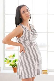 Schwangerschaftstests. depressive schwangere frau, die die hände auf dem rücken hält und die augen geschlossen hält