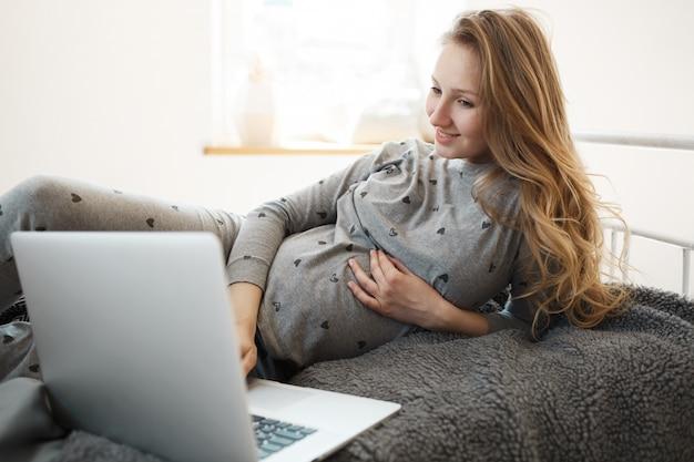 Schwangerschaftszeit mit freude verbringen. schöne blonde junge schwangere frau in der bequemen hauptkleidung, die auf bett liegt, auf der suche nach einem guten film ist, um auf laptop zu sehen, sich zu entspannen, hand auf ihrem bauch zu halten.