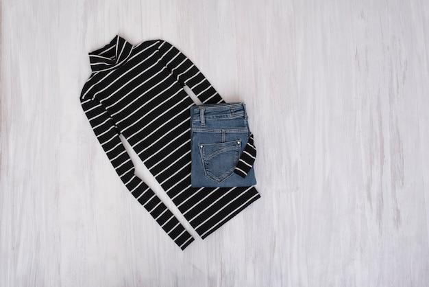 Schwarz gestreifter rollkragenpullover und jeans auf holzuntergrund. modisches konzept
