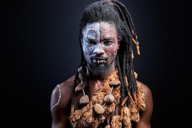 Schwarz mit schamanen aborigen make-up selbstbewusst, schwarzer typ isoliert im studio. porträt