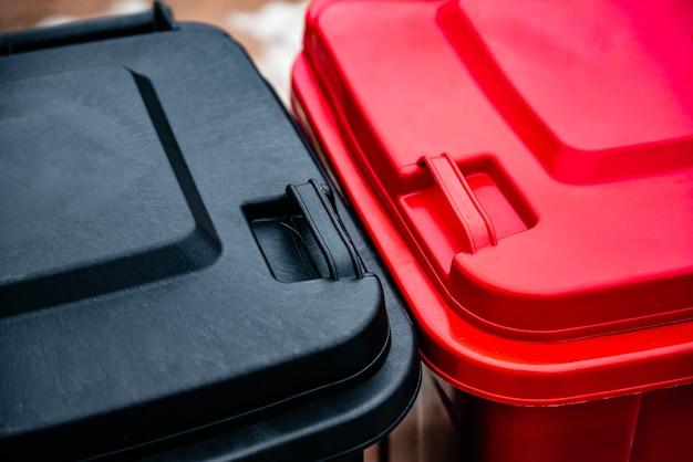 Schwarz-rote müllcontainer zum trennen und sortieren von glas, plastik, papier und hausmüll. mülltrennung, das konzept der umweltfreundlichen müllabfuhr.